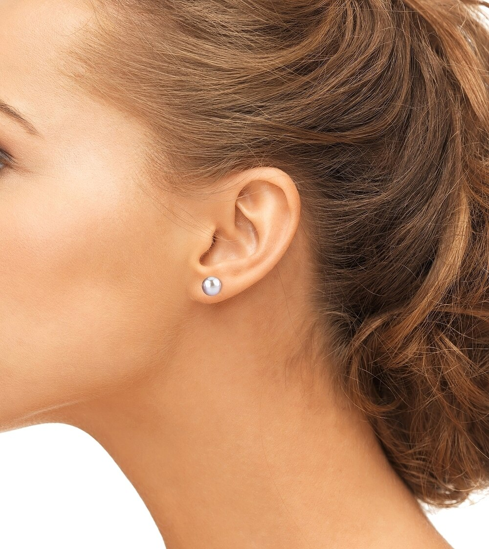 Classic gold stud earrings feature two 10.0mm peach Freshwater pearls, selected for their luminous luster